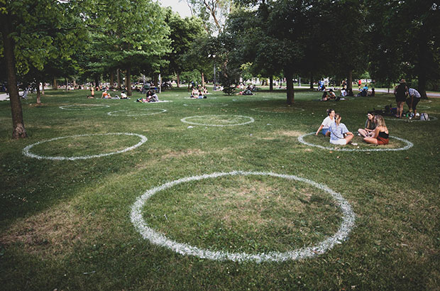 Groups of people in a park are clustered inside marked circles to demonstrate the changes in public spaces during COVID19