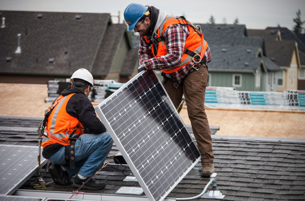 Two workers installing a solar panel on a roof