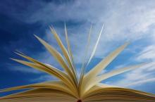 Photo of open book with blue sky in background